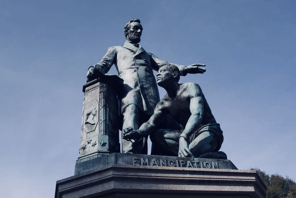 "A statue of Abraham Lincoln with his hand on a pillar that has the silhouette of George Washington. Lincoln is standing with his over a kneeling Black man. The word ""Emancipation"" is inscribed on the statue's base."